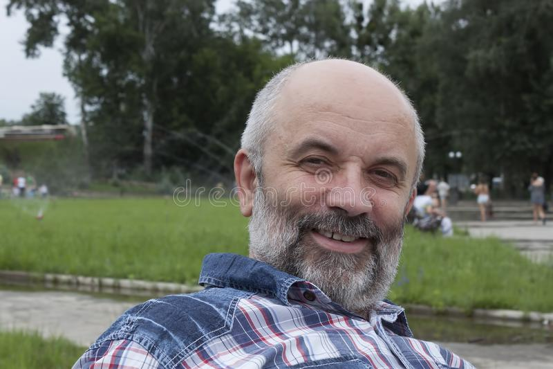 成熟年龄的一个人,秃头与一个胡子,在格子衬衫特写镜头 免版税库存照片