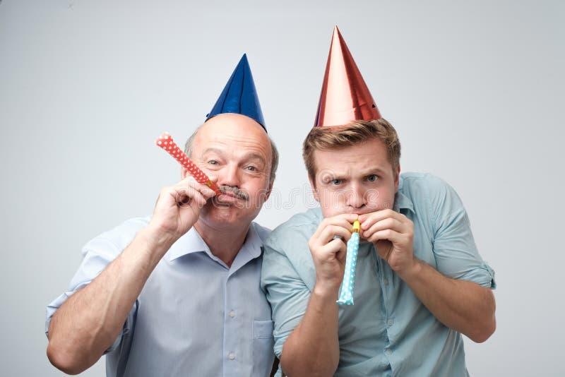 成熟庆祝生日快乐的人和他的年轻儿子戴着滑稽的帽子 免版税库存图片