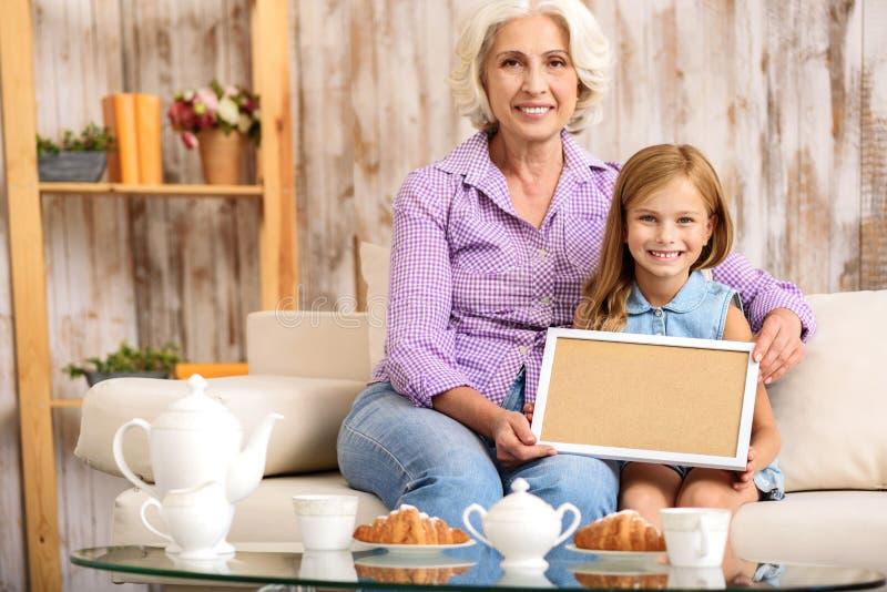 成熟当前有趣的照片的夫人和她的孙 免版税图库摄影
