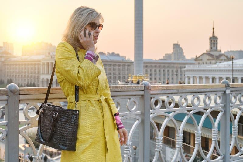 成熟微笑的妇女,黄色外套城市画象玻璃的谈话在手机,背景都市全景,拷贝空间 免版税库存图片