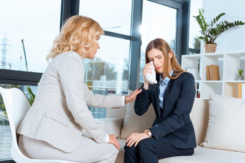 成熟心理学家支持的哭泣的少妇 免版税库存图片