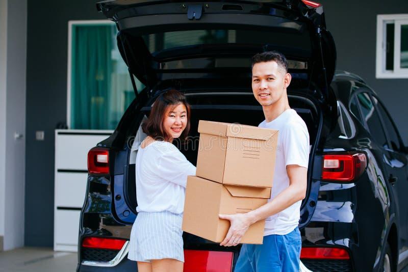 成熟愉快的亚洲人在新的家与从车厢的夫妇运载的纸板箱结婚 图库摄影