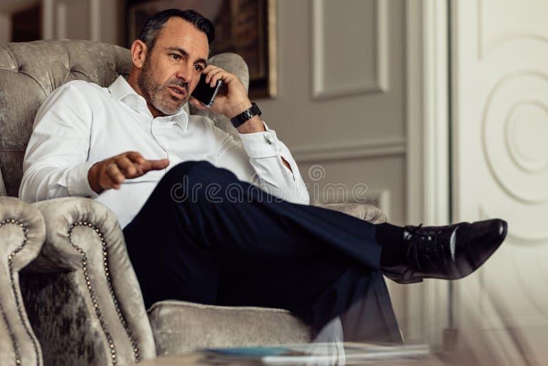 成熟打电话的旅客商人佩带的白色衬衫在到达以后在酒店房间 旅客坐长沙发和 库存照片