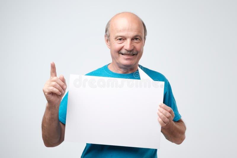 成熟拿着空白的纸片的蓝色T恤杉的秃头人,微笑 图库摄影