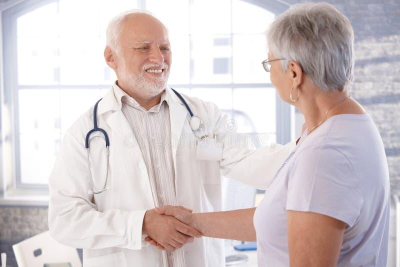 成熟握手的医生和高级患者 免版税库存照片