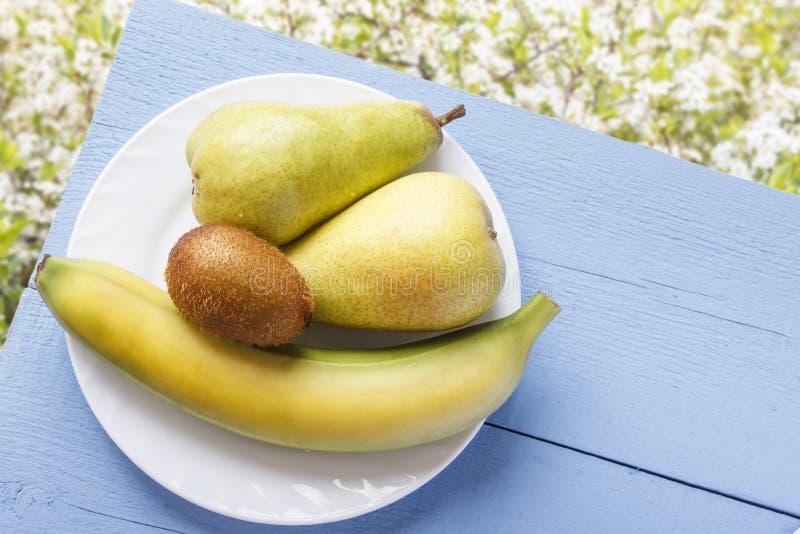 成熟新鲜水果在木蓝色桌上和在自然白花背景 香蕉、猕猴桃和梨素食breakfa的 库存照片