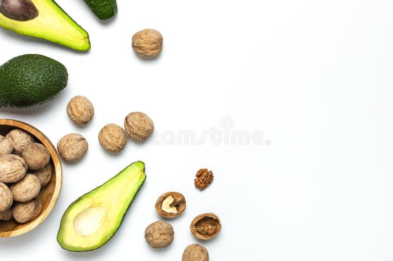 成熟新鲜的鲕梨和核桃在木碗在白色背景顶视图平的被放置的拷贝空间 果子健康食品概念,饮食 库存照片