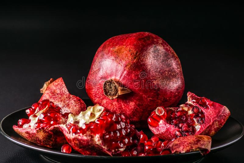 成熟新鲜的pomengranate果子,在黑背景 图库摄影