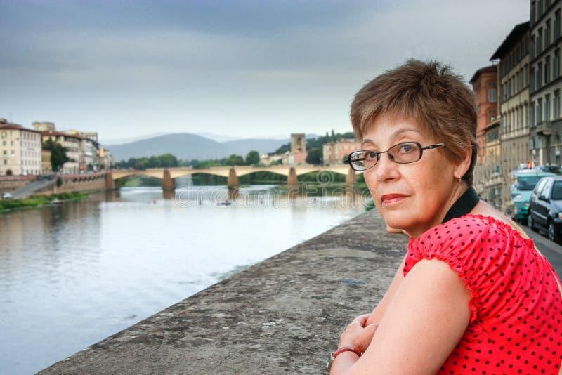 成熟旅游妇女停留反对在亚诺河河的桥梁在佛罗伦萨 免版税图库摄影