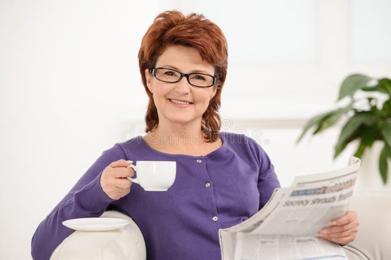 成熟有报纸的夫人,当喝咖啡时 库存图片
