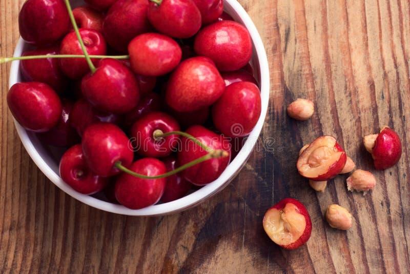 成熟有机本地出产的樱桃和石头在葡萄酒陶瓷碗 库存照片
