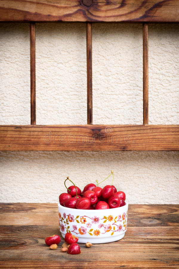 成熟有机本地出产的樱桃和石头在葡萄酒陶瓷碗 免版税库存照片