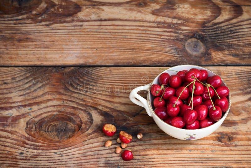 成熟有机本地出产的樱桃和石头在葡萄酒陶瓷碗 免版税库存图片