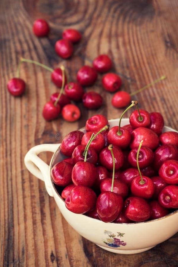 成熟有机本地出产的樱桃和石头在葡萄酒陶瓷碗 库存图片
