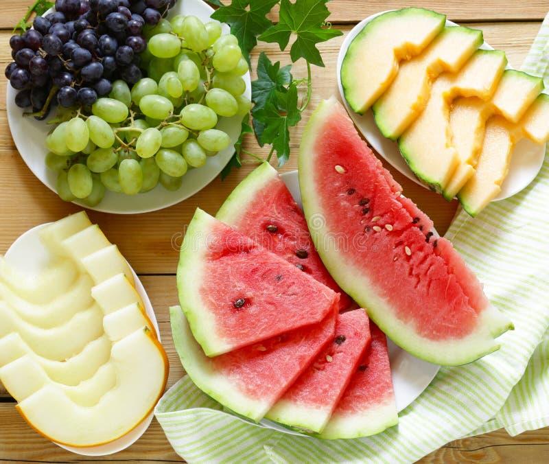成熟有机果子西瓜、瓜甜瓜和葡萄在一张木桌上 库存图片
