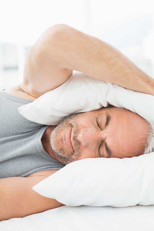 成熟有枕头的困人覆盖物耳朵在床上 库存照片
