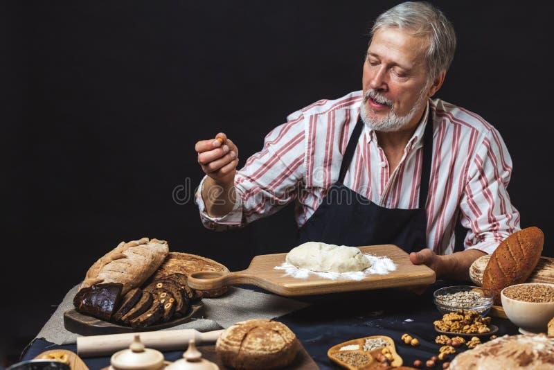 成熟有胡子的面包的面包师人揉的面团在桌上 免版税库存图片