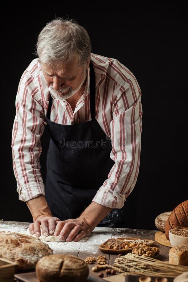 成熟有胡子的面包的面包师人揉的面团在桌上 库存照片