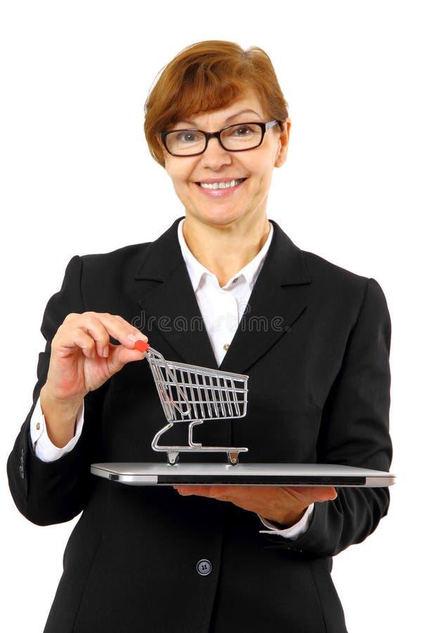 成熟有购物车的,膝上型计算机红发女商人 免版税库存照片