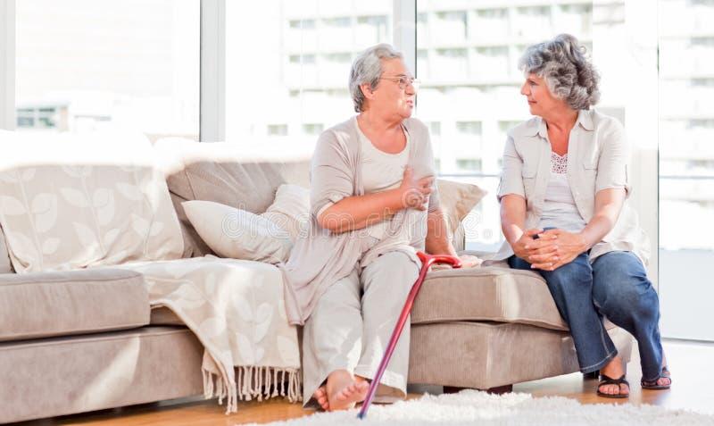 成熟朋友联系在沙发 免版税库存照片