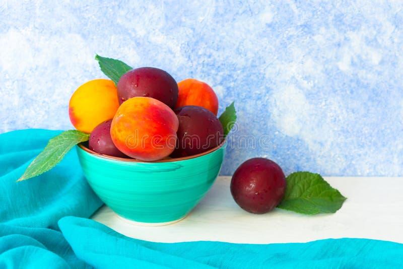 成熟李子和桃子在一块蓝色板材在蓝色背景 r 免版税图库摄影