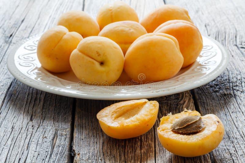 成熟杏子人群在白色木背景的 免版税库存图片