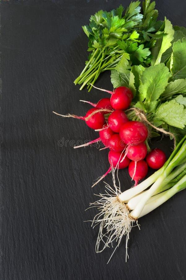 成熟束红色萝卜,葱,与叶子的荷兰芹在作为背景的一个黑盘 顶视图 沙拉的成份 免版税图库摄影