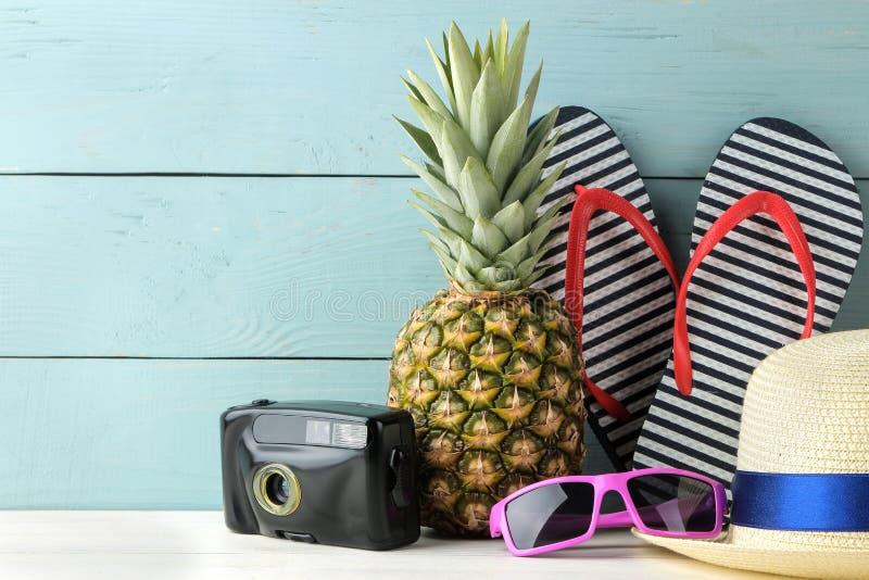 成熟果子菠萝和海滩辅助部件、太阳镜、照相机、触发器和帽子在蓝色木背景 ?? 空间为 免版税图库摄影