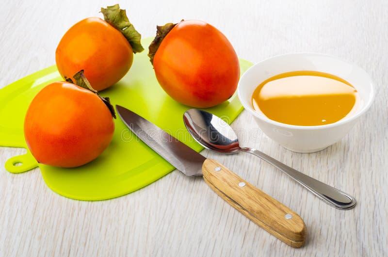 成熟柿子,刀子,在切板,有细磨刀石的碗的茶匙 免版税库存照片