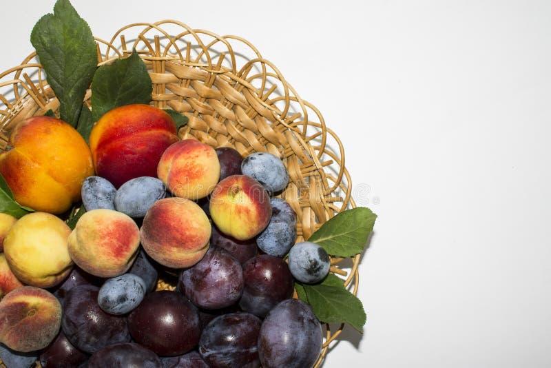 成熟桃子和李子在一个小篮子 库存照片