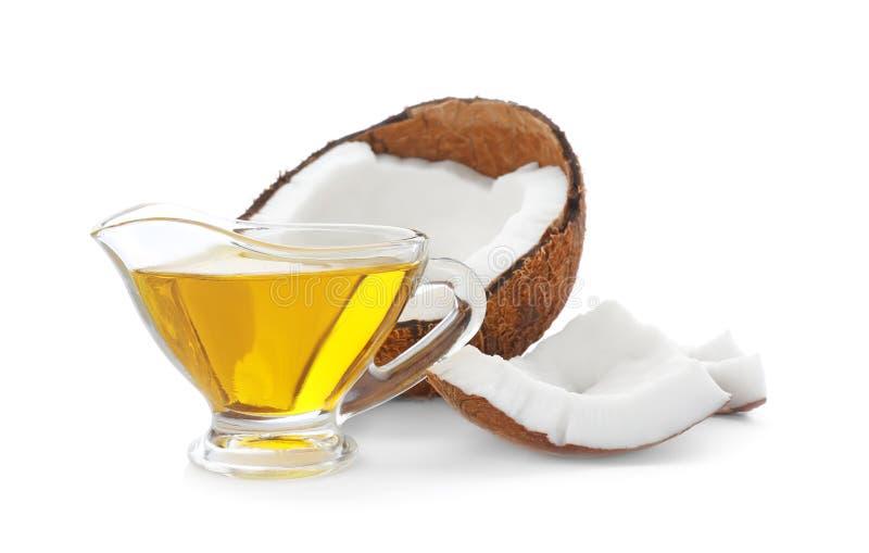 成熟椰子和调味汁瓶有油的在白色背景 免版税库存照片