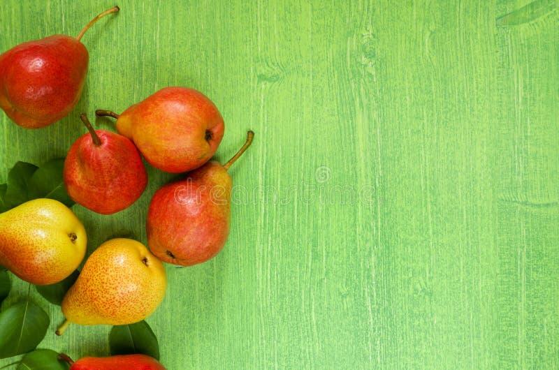 成熟水多的红色梨和叶子在木选材台背景, 免版税图库摄影
