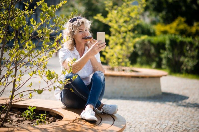 成熟点击selfie的妇女,当享受donught时 免版税库存照片