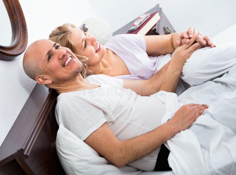 成熟爱恋的夫妇lounging在床上在醒拥抱以后 免版税图库摄影