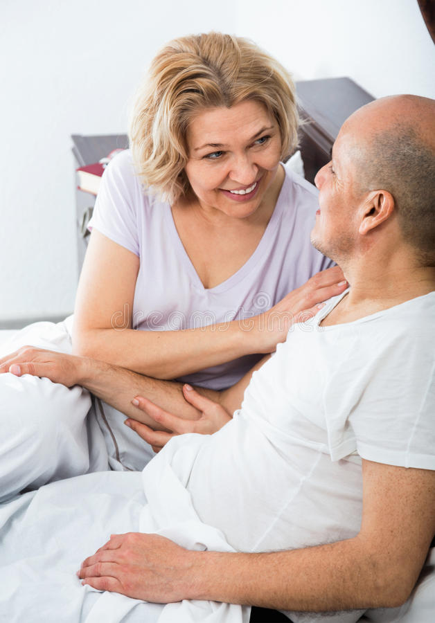 成熟爱恋的夫妇lounging在床上在醒拥抱以后 库存图片
