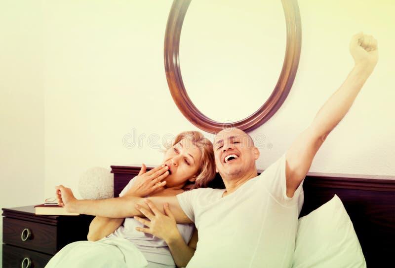 成熟爱恋的夫妇lounging在床上在醒拥抱以后 库存照片