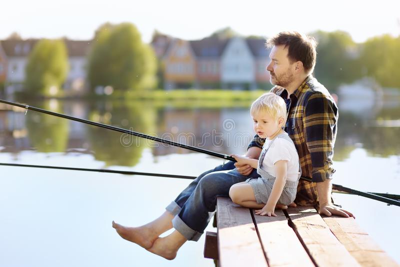 成熟爸爸和一点儿子钓鱼在湖或河在周末 户外家庭的夏天活动与孩子 库存照片