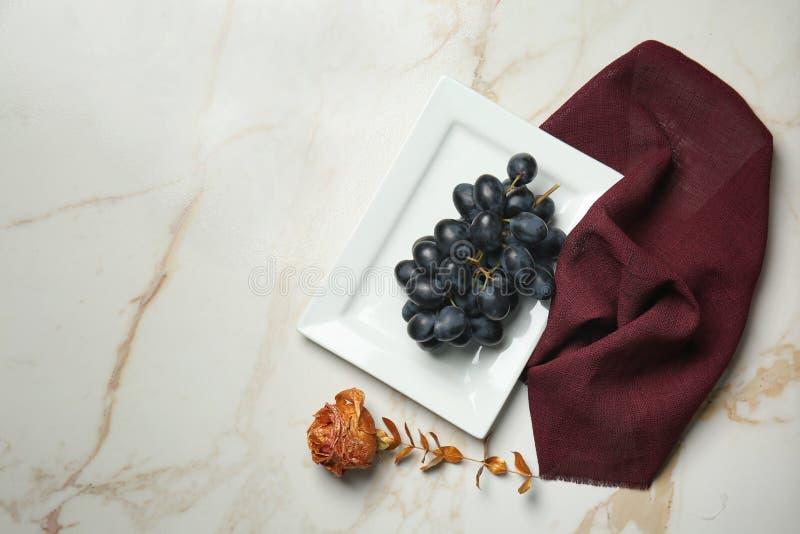 成熟甜葡萄和金黄玫瑰在轻的桌上 免版税库存照片