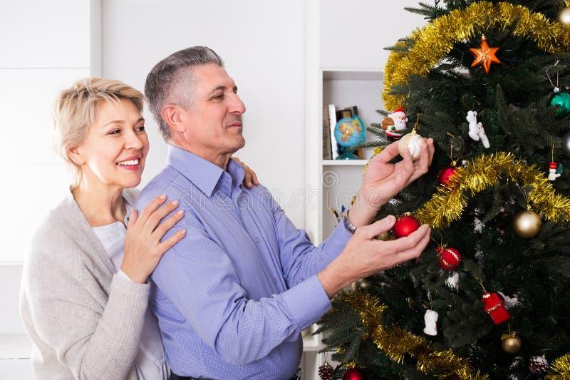 成熟男人和妇女是挂上新年在冷杉木的` s玩具 免版税图库摄影