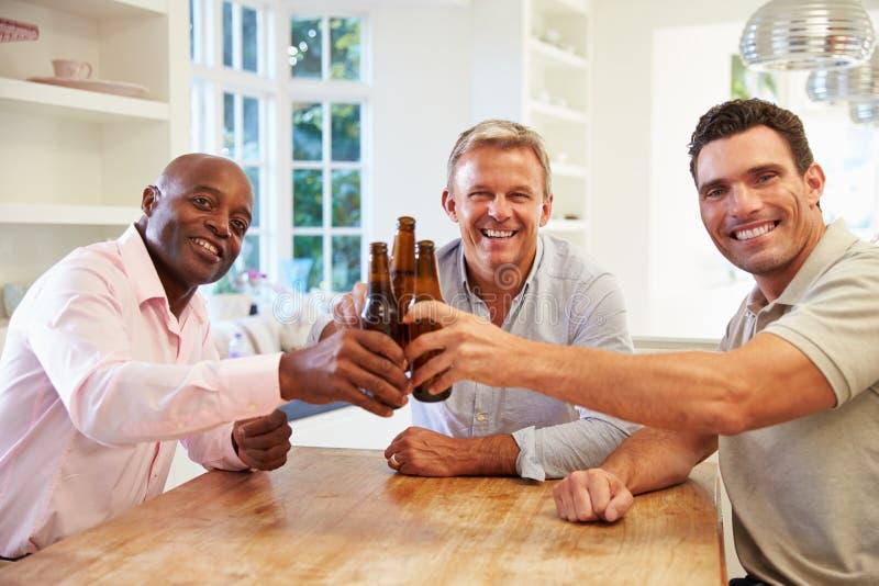 成熟男性朋友坐在表饮用的啤酒和谈话 免版税图库摄影