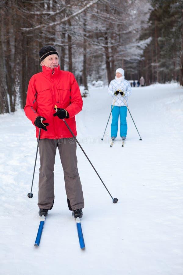 成熟男性滑雪者和妇女在冬天雪滑雪坡道的滑雪停留 库存照片