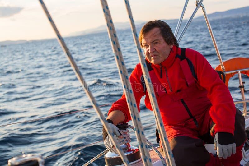成熟男性船长坐他的航行游艇 体育运动 免版税库存图片