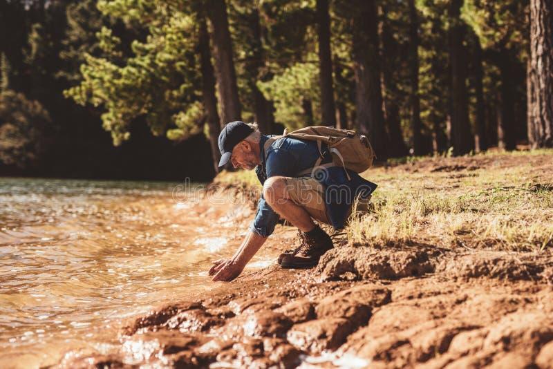 成熟男性远足者洗涤的面孔在湖 库存照片