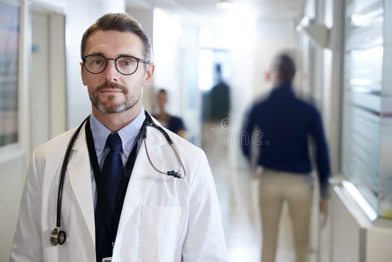 成熟男性Wearing White Coat With医生听诊器画象在繁忙的医院走廊的 图库摄影