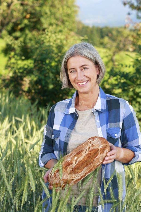 成熟的农厂妇女用新近地被烘烤的面包 免版税库存图片