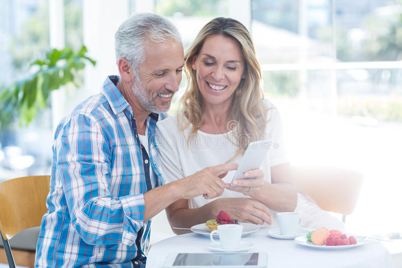 成熟看在手机的夫妇,当坐在餐馆时 库存照片