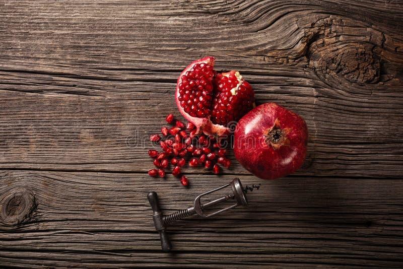 成熟石榴果子和一个拔塞螺旋在木背景 库存照片