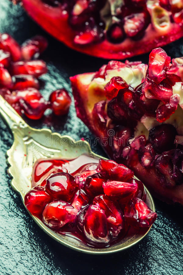 成熟石榴片断和五谷  能胆固醇接近的更低的宏指令一石榴种子射击superfoods 一部分的在花岗岩板和古董匙子的石榴果子 图库摄影