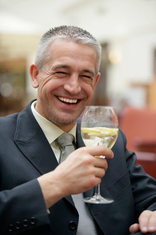 成熟矿泉水商人饮用的酒杯  免版税库存图片
