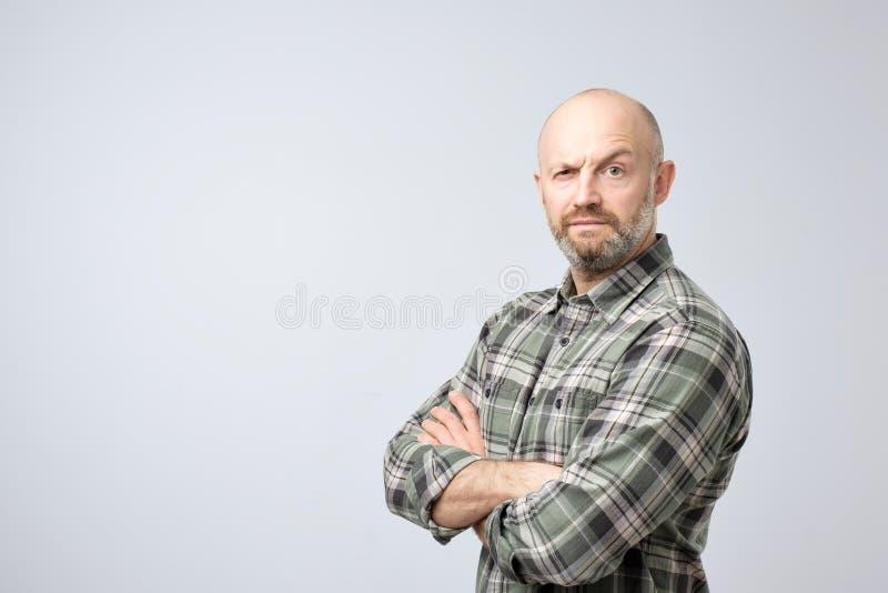 成熟站立与胳膊横渡和严肃的面孔的方格的衬衣的秃头人在照相机,看起来可疑 库存图片